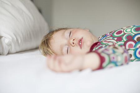 king bed: blonde caucasian baby face nineteen month age with colored shirt sleeping on white sheets king bed