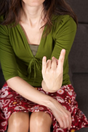 fuck: woman detail sitting on a brown sofa gesturing fuck off