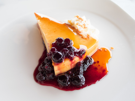 confectionery: piece of cheese cake orange jam with strawberry jam with red fruits berries almond chopped and whipped cream on white modern dish over white tablecloth restaurant