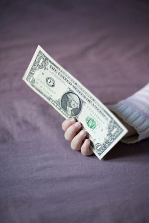 somnolent: closeup one dollar banknote in hand of blonde caucasian baby nineteen month age with pink and white stripped jersey sleeping on brown sheets king bed