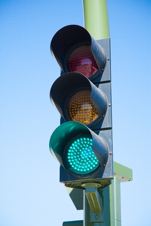 traffic light semaphore green light on orange and red lights off  in green pole on blue sky
