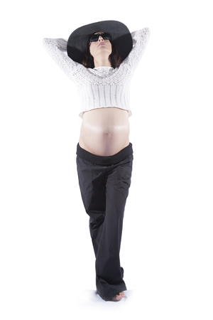 belly button: eight months brunette pregnant woman bare tummy belly button wool top sweater black sunglasses big pamela hat posing as fashion model isolated on white