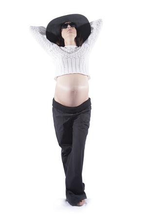 ombligo: ocho meses morena mujer embarazada vientre desnudo boca abajo su�ter de lana bot�n superior gafas de sol negras gran sombrero posando pamela como modelo de manera aislada en blanco Foto de archivo
