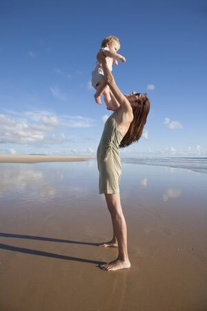 blonde females: one year blonde baby fly in green dress woman mother arms at beach next to Conil Cadiz Spain Stock Photo