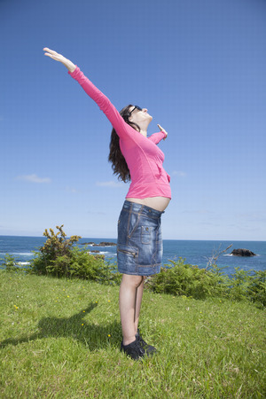 expectant arms: open arms pregnant woman with pink jersey at Asturian coast Stock Photo