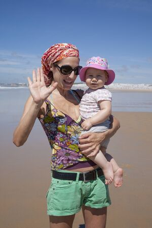 pink hat: happy woman with sunglasses green shorts headscarf and baby pink hat in arms at beach Conil Cadiz Spain