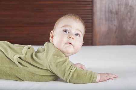 six months: six months age blonde baby green velvet onesie lying on white sheet bed with brown wood background face looking surprised Stock Photo