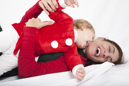 accomplices: tender and funny portrait of one year age caucasian blonde cute lovely baby Santa Claus Christmas disguise with brunette woman mother red cardigan green sweater embraced laughing together lying on white floor background Stock Photo