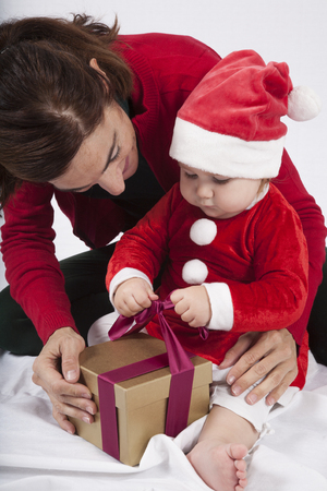 red cardigan: one year age caucasian blonde baby Santa Claus disguise with brunette woman mother red cardigan green trousers opening golden box gift Christmas on white background Stock Photo