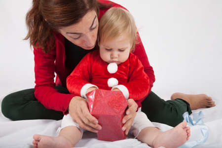 red cardigan: one year age caucasian blonde baby Santa Claus disguise with brunette woman mother red cardigan green trousers opening Christmas box gift on white background