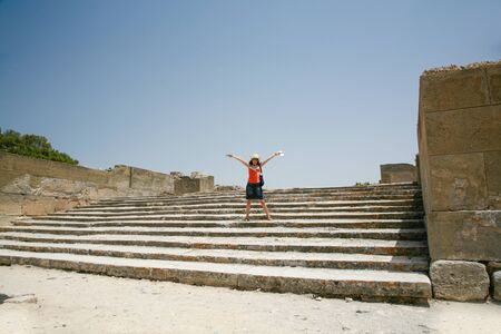xv century: woman traveler tourist open arms in landmark stairs of Festo or Festos palace ruins, from XV century Before Christ, Minoan greek city monument in Crete Greece Europe Stock Photo