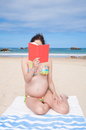 enceinte: brunette brown hair pregnant woman with bikini sitting on towel reading red book hiding face in summer in holidays beach in Asturias Spain