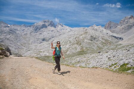 victory symbol: brunette sport woman with green shirt brown trousers walking or hiking or trekking on rural path in Picos de Europa mountains in Cantabria Spain gesturing victory symbol with finger hands Stock Photo