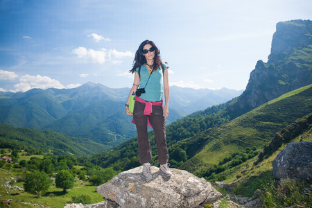 picos: brunette sport hiking or trekking woman with green shirt brown trousers and sunglasses posing looking over valley and mountain in Picos de Europa natural park in Cantabria Spain