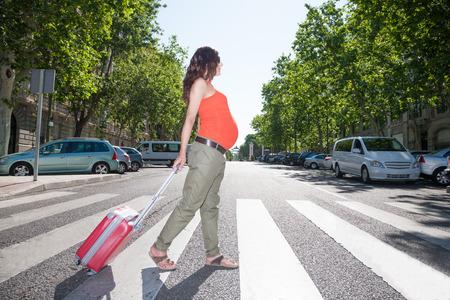 brune cheveux bruns femme enceinte avec chemise orange pantalon vert et lunettes de soleil en été à pied avec une valise sur passage pour piétons à Madrid rue urbaine