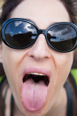 derision: close-up of face brunette woman with black sunglasses looking and teasing sticking-out tongue to camera