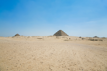 djoser: landscape of Egyptian desert, with archeological area and far Saqqara stepped Pyramid of Djoser, from year 2648 Before Christ, next to ancient Memphis city, in Egypt, Africa