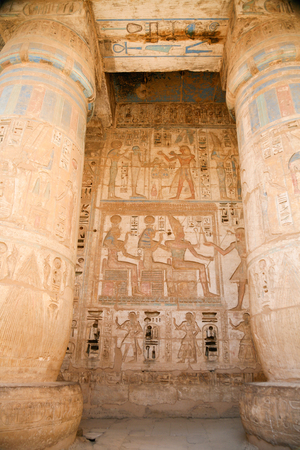 wall paintings: Egyptian paintings, carving figures and hieroglyphs in columns and wall of landmark Temple of Ramses or Ramesses III at Medinet Habu, monument in Luxor, Egypt, Africa Stock Photo