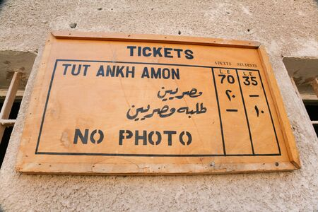 tariff: wooden placard with rates, tickets and no photo, in Egyptian Tut Ankh Amon tomb, or Tutankhamun, in landmark Kings Valley, in Egypt, Africa