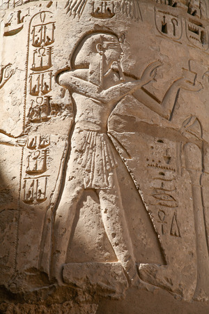 Egyptian carving figure and hieroglyphs in column of landmark Temple of Ramses or Ramesses III at Medinet Habu, monument in Luxor, Egypt, Africa Stock Photo