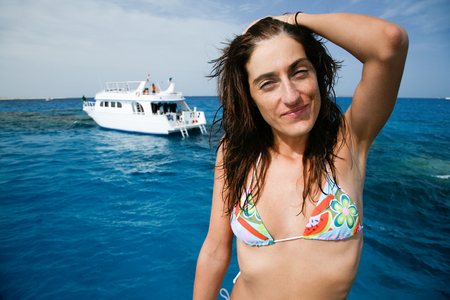 brunette woman in bikini, hand in hair looking, behind a boat or yacht ready to diving in blue ocean water in Red Sea, next to Sharm al Sheij and Hurghada, Egypt, Africa