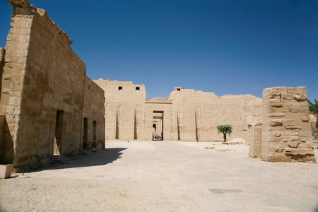 mortuary: wall front facade of landmark Egyptian mortuary Temple of Ramses or Ramesses III at Medinet Habu, monument with carving figures and hieroglyphs, in Luxor, Egypt, Africa Stock Photo