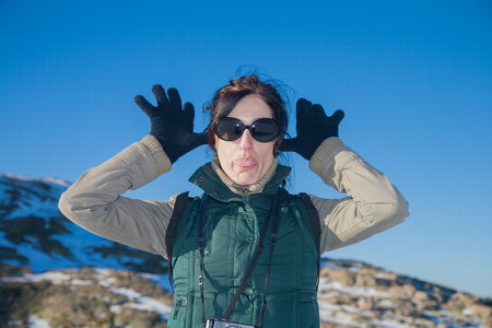 sticking out tongue: portrait of pretty face woman with green vest and sunglasses looking gesturing hands gloves, making fun scoff and sticking out tongue, in winter outdoor blue sky
