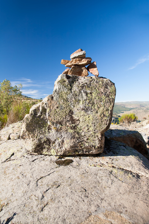 milestone: pile or heap of stones several sizes leading mountain path as cairn or milestone and horizon blue sky in Gredos, Avila, Spain, Europe Stock Photo