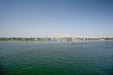 thebes: landscape from water Nile River with boats, green trees and desert mountain, next to ancient Thebes, in Luxor, Egypt, Africa