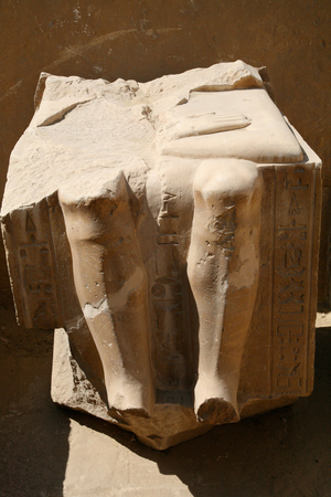 carved stone: piece of egyptian sculpture, carved stone block with knees, legs and hieroglyphs, in Egypt, Africa Stock Photo