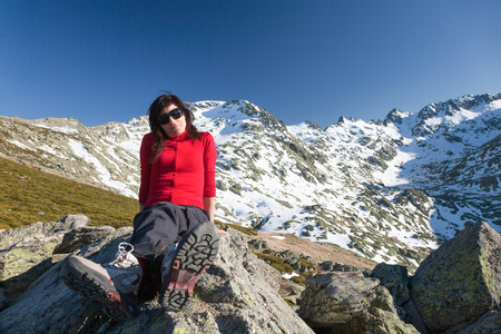 red cardigan: brunette sport woman red cardigan, black trousers and sunglasses sitting relaxing and posing looking on rock blue sky and snow peak mountain in Gredos, Avila, Spain, Europe