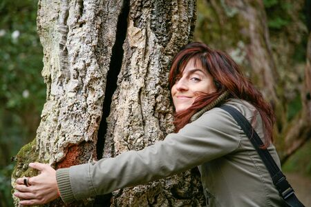 face in tree bark: woman green jacket laughing looking hugging or embraced a trunk tree in a forest or park Stock Photo