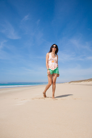 derision: brunette summer vacation woman with sunglasses, white shirt and green shorts standing gesturing sticking out tongue on sand with ocean, in Zahara beach, Cadiz, Andalusia, Spain, Europe