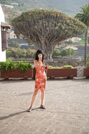 millennial: brunette woman with orange dress looking to camera, as photographer taking photo picture, behind The Drago Tree, famous landmark millennial plant, in Icod, Tenerife, Canary Islands, Spain, Europe