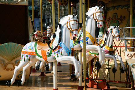vivo: detail of white horses and carriage in a carousel, roundabout or merry-go-round retro style
