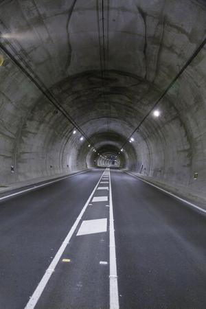 dividing lines: landscape straight grey lonely road tunnel with two lanes, white painting dividing lines in asphalt and light, in Spain Europe Stock Photo