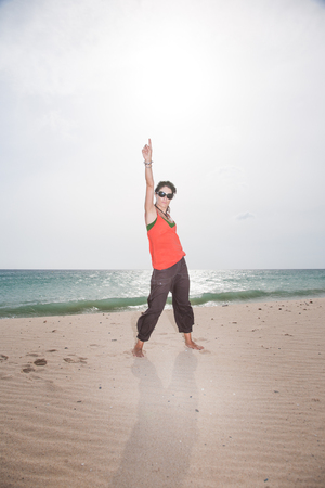 tarifa: brunette summer vacation woman with sunglasses, orange shirt and brown trousers standing finger and hand up on sand with ocean behind, in Lances beach, Tarifa, Cadiz, Andalusia, Spain, Europe Stock Photo