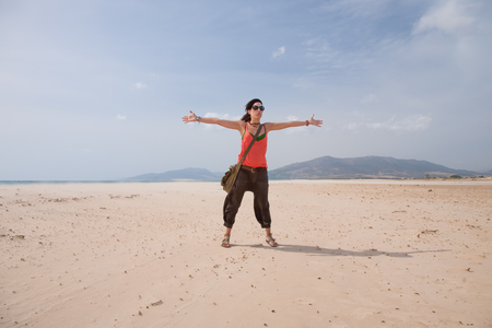 tarifa: brunette summer vacation woman with sunglasses, orange shirt and brown trousers standing open arms up embracing on sand greeting wind, in Lances beach, Tarifa, Cadiz, Andalusia, Spain, Europe