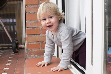 nineteen: portrait of blonde caucasian baby nineteen month age chubby face looking at camera peering terrace floor supported on the arms Stock Photo