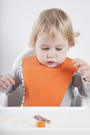 baby rice: blonde caucasian baby seventeen month age orange bib grey sweater eating meal in white high-chair surprised looking at carrot and tuna Stock Photo