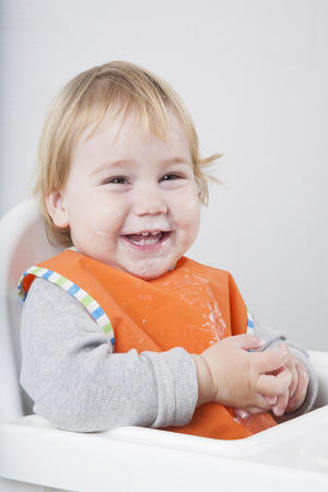 high chair: blonde caucasian baby seventeen month age orange bib grey sweater on white high chair laughing looking at camera eating Stock Photo