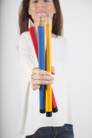 primary colours: closeup of blue red and yellow primary colours big pencils in woman hand fingers isolated over white background