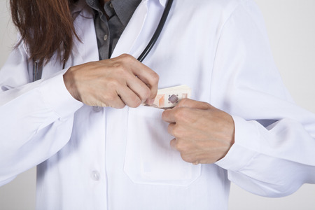 woman doctor hands with white gown and stethoscope tucking a wad of Euro banknotes in her pocket Stock Photo