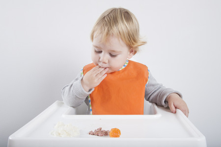 highchair: blonde caucasian baby seventeen month age orange bib grey sweater eating meal with her hand in white high-chair