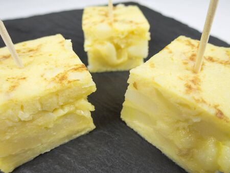 portions: little portions with toothpick of yellow spanish potato omelette on black slate tray Stock Photo