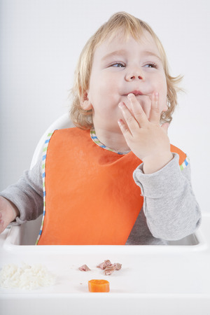 highchair: blonde caucasian baby seventeen month age orange bib grey sweater eating meal in white high-chair surprised looking at carrot and tuna Stock Photo
