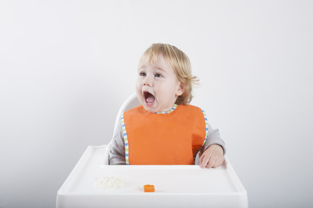 highchair: blonde caucasian baby seventeen month age orange bib grey sweater eating rice carrot on white high-chair laughing and smiling