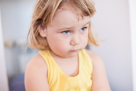 lament: portrait of blonde two years old child with yellow shirt looking with sad face Stock Photo