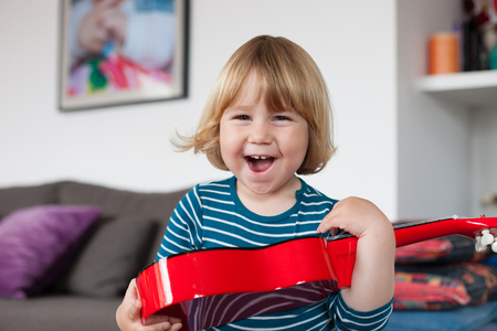spanish looking: blonde two years old child with striped blue and white sweater inside home with red spanish little guitar in her hands laughing happy looking at camera Stock Photo