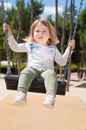 teeter: two years old blonde kid with white shirt and green trousers teeter in swing at urban park Stock Photo